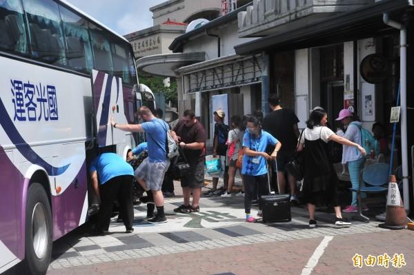 恆春居民及遊客在炎熱天候克難候車。(記者蔡宗憲攝)