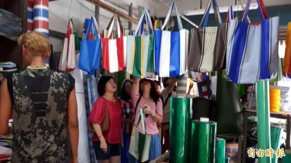 外地遊客到帆布行選購彩色帆布手提袋。(記者黃明堂攝)