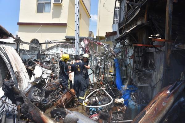 火災現場堆滿雜物,消防人員正在找尋屋主下落。(記者葉永騫攝)