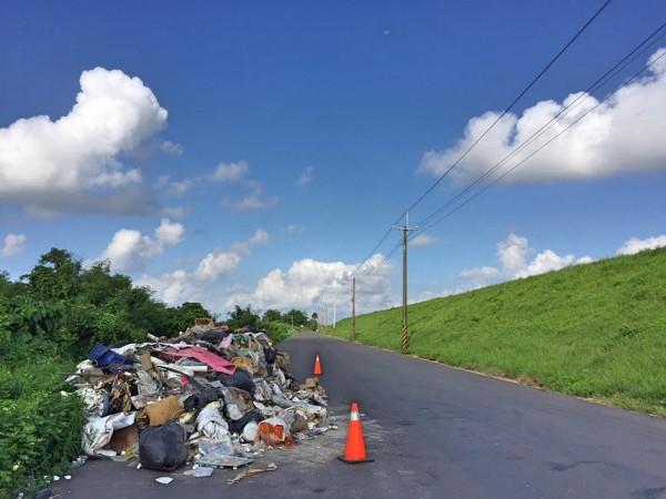 曾文溪南岸道路,遭人棄置一大堆廢棄物。(圖由翁育民提供)