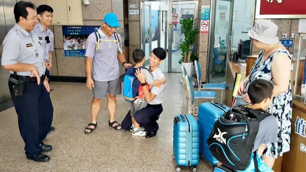 6歲的孫小弟弟陪家人從台北到高雄為參加羽球賽的哥哥加油,他卻在飯店走失後尋獲,副所長陳威宇抱抱他安撫情緒。(記者黃良傑翻攝)