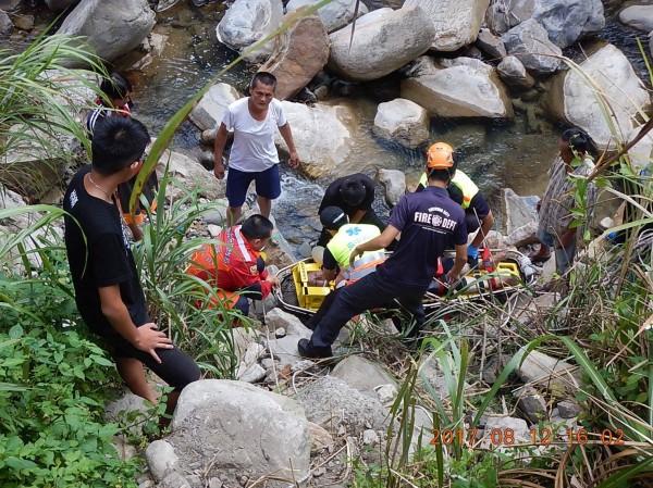 搜救人員將墜谷的林男放上擔架固定,準備抬上岸。(記者李忠憲翻攝)
