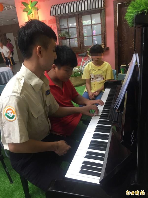 許峯瑞義務教少教所孩子彈琴。(記者羅欣貞攝)
