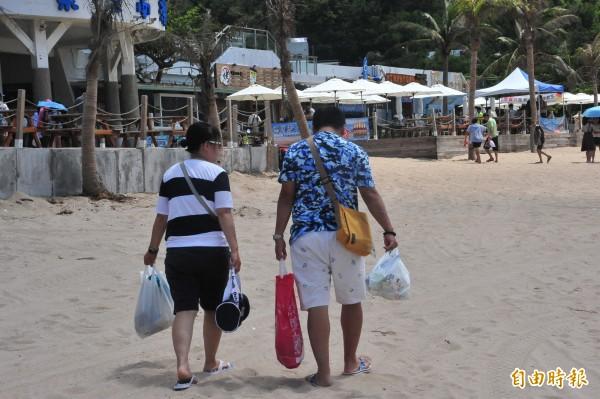 不少遊客受感動,自動帶走垃圾。(記者蔡宗憲攝)