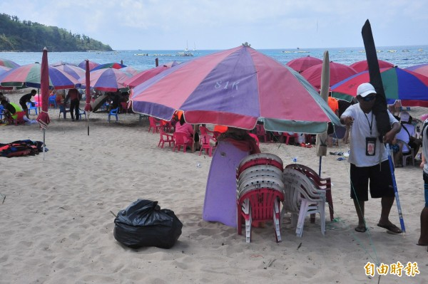 業者帶大垃圾袋自發清潔海灘。(記者蔡宗憲攝)