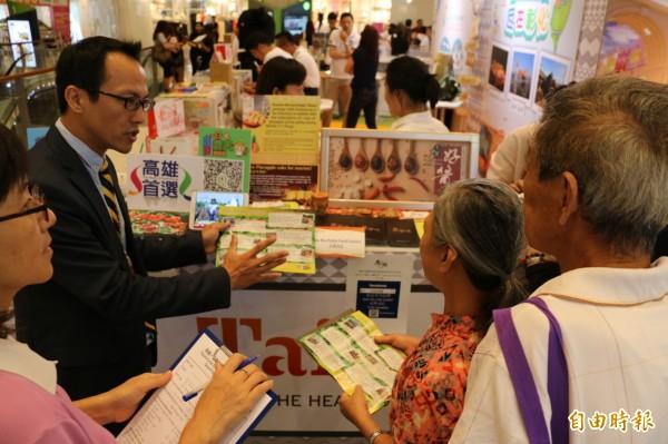 農業局挺進新加坡國際旅展,科長方啟峰(左穿西裝者)親自招商,說明一日農夫遊程。(記者陳文嬋翻攝)