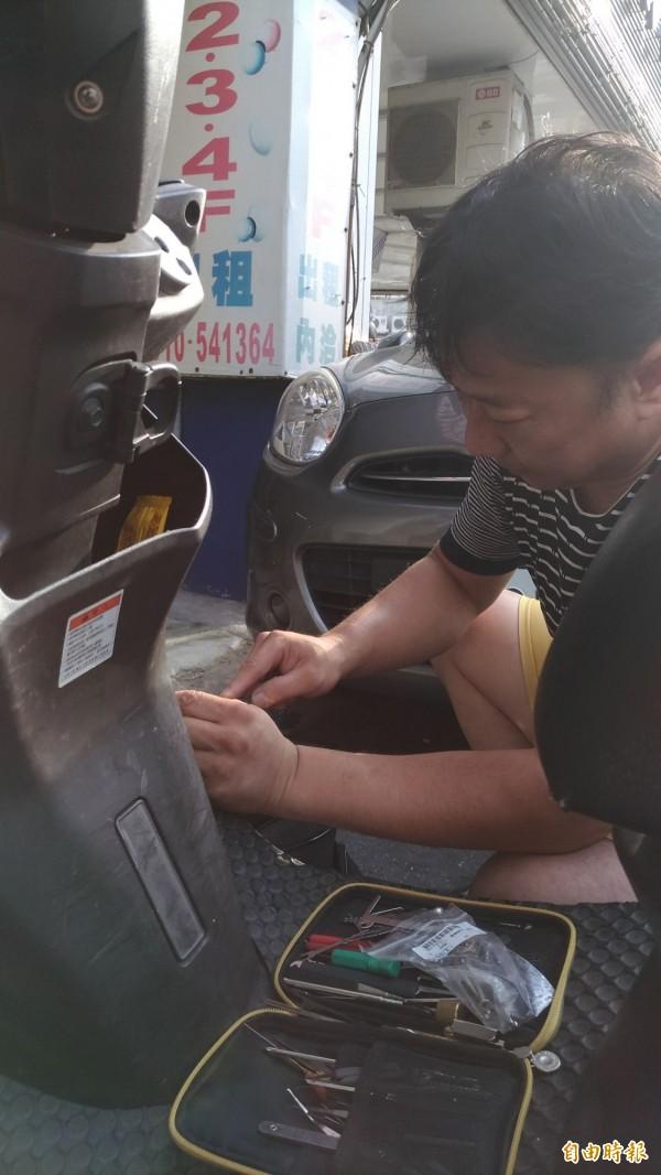 客人機車鑰匙掉了,阿圳冒著烈日揮汗開車鎖。(記者許國楨攝)