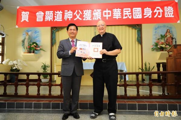 台中市長林佳龍(左)頒發身分證給曾顯道神父。(記者張軒哲攝)