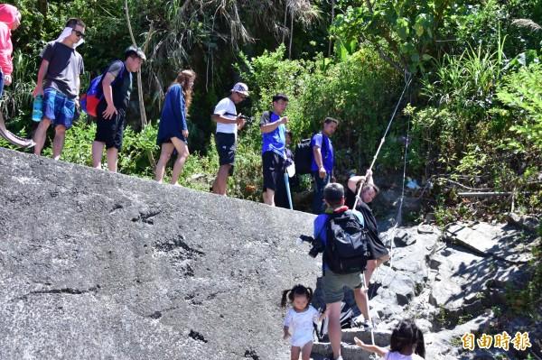 要通往粉鳥林小海灘,得攀爬唯一的一條通道,遊客行經常險象環生。(記者張議晨攝)