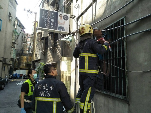 受困鐵窗上的屋主吳男被誤認是小偷,消防獲報破窗救人。(記者吳仁捷翻攝)