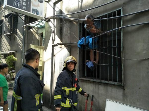 蔡男回家發現沒帶鑰匙,想爬鐵窗進家門反倒卡在鐵窗上進退不得。(記者吳仁捷翻攝)