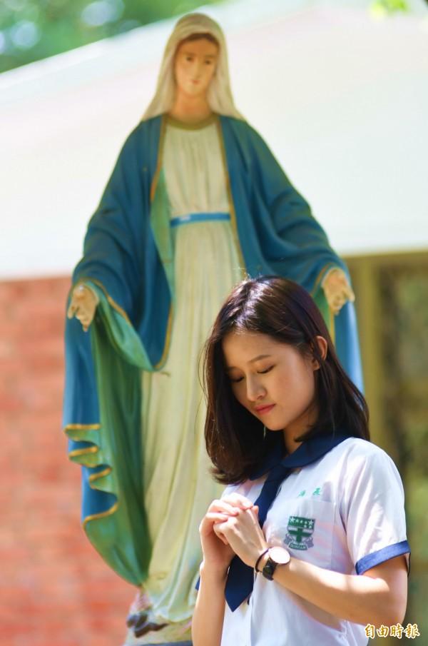 花蓮天主教海星中學由聖吳甦樂女修會創辦,修女雕像慈愛地俯視祈禱的少女。(記者花孟璟攝)