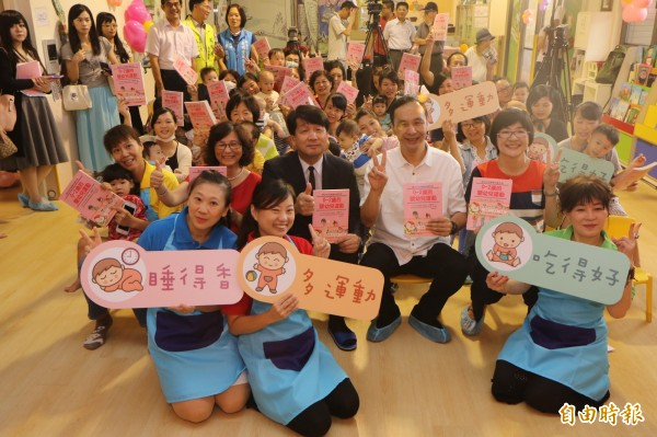 新北市長朱立倫今天出席日本日本早稻田大學腦科學及嬰幼兒發展專家前橋明的新書發表會,與重新公托中心的家長、孩子、幼保老師合影。(記者葉冠妤攝)