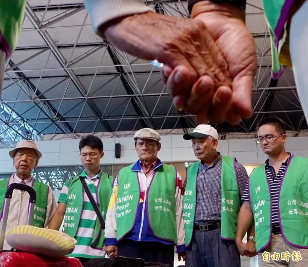 由台灣聯合國協進會所組成的「台灣加入聯合國宣達團」25名成員,8日晚間在團長蔡明憲(中)率領下搭機赴美,成員在搭機前牽手禱告,祈求此行圓滿順利。(記者朱沛雄攝)