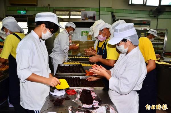 長榮女中的學生也幫忙憨兒們趕製月餅。(記者吳俊鋒攝)