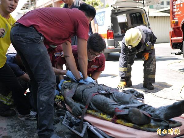 消防人元將人拉出後送往醫院急救。(記者簡惠茹攝)