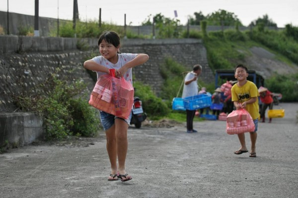 小孩提著金銀紙,走上濁水溪堤防,跟著長輩拜溪王。(圖:許震唐提供)