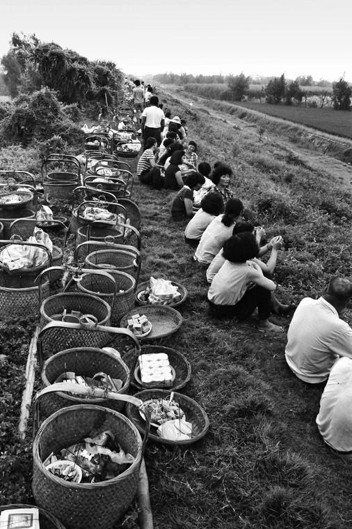 28年前,濁水溪河堤未整治水泥護堤,家家戶戶挑著扁擔,坐在土堤等待準備祭拜溪王。(圖:許震唐提供)