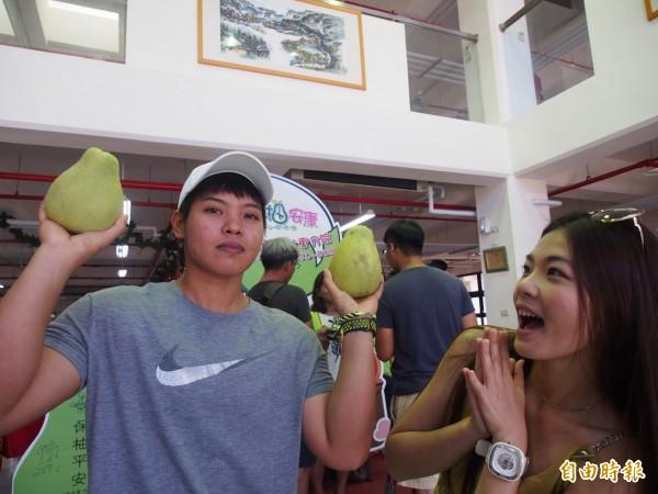 洪萬庭(左)舉起老欉文旦,力挺創世台東院的義賣助植物人雙軌服務經費。(記者王秀亭攝)