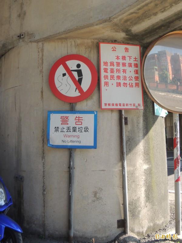 竹北市經國橋下有設置「禁止丟棄垃圾」的警告牌,但地上仍可見空瓶罐等垃圾。(記者廖雪茹攝)