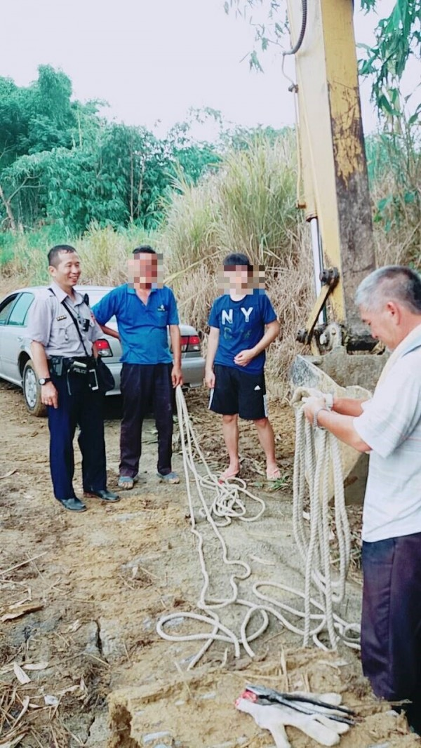 民雄警分局北斗所派出所副所長吳明誠(左1)請挖土機駕駛(右1)協助,幫助誤入鳳梨田的轎車脫困。(記者曾迺強翻攝)