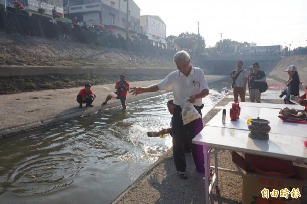 大士爺廟工作人員將供品投入溪流中,敬獻「好兄弟」。(記者曾迺強攝)