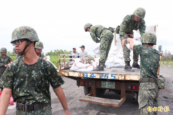 陸軍蘭陽指揮部國軍弟兄今上午至公館海灘裝填沙包。(記者林敬倫攝)