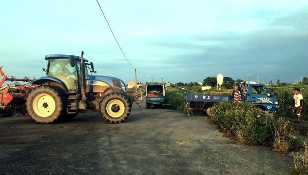 兩台貨車接連陷入沼澤,無法動彈,警方靈機一動,請農人開耕耘機來拉車。(記者林宜樟翻攝)