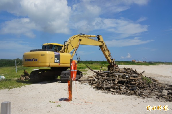 澎湖縣環保局雇請怪手,清除沙灘上漂流木。(記者劉禹慶攝)