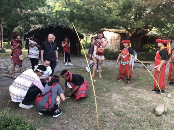 原住民獵人教室可讓遊客親自製作陷阱,寶拉也拿起相機拍照記錄。(圖由泰雅渡假村提供)