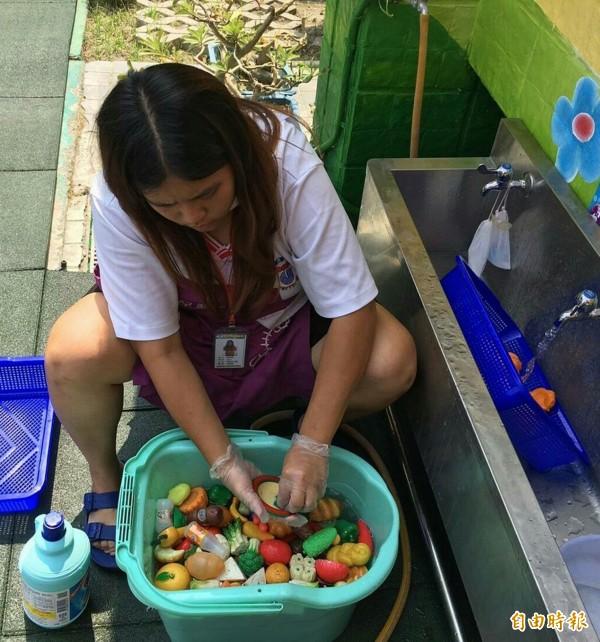 高雄鳥松區的菁華幼兒園老師們,每天趁著午休時間,用漂白水消毒玩具。(記者張忠義攝)