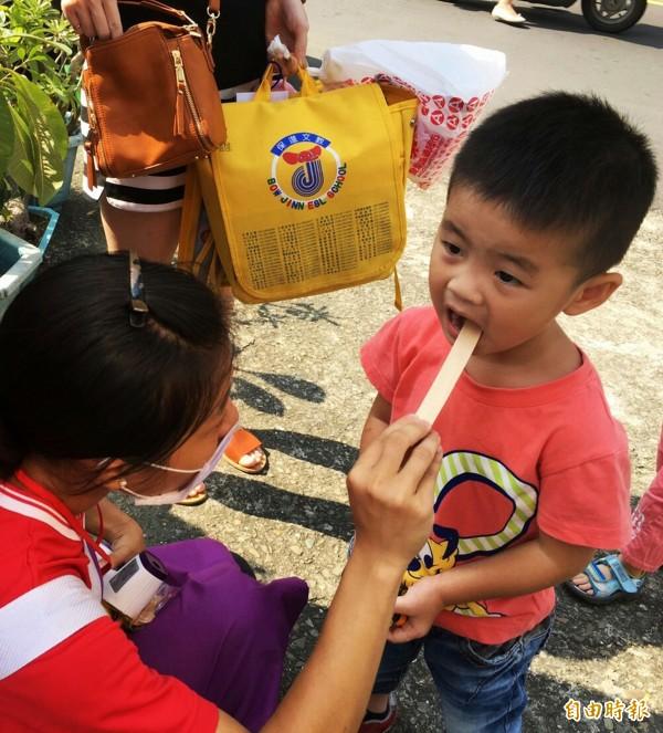 幼兒園老師為學童檢查口腔黏膜、舌頭、牙齦和嘴唇,是否出現水泡潰瘍等腸病毒症狀。(記者張忠義攝)