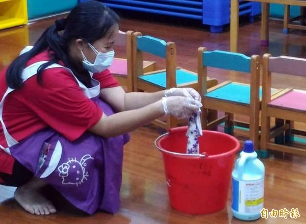 菁華幼兒園老師們趁著午休時間用漂白水擦拭課桌已消毒。(記者張忠義攝)
