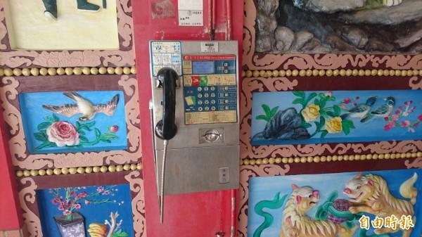 北門井仔腳聚落就只剩這支公用電話,設在當地泰安宮廟前壁堵。(記者楊金城攝)