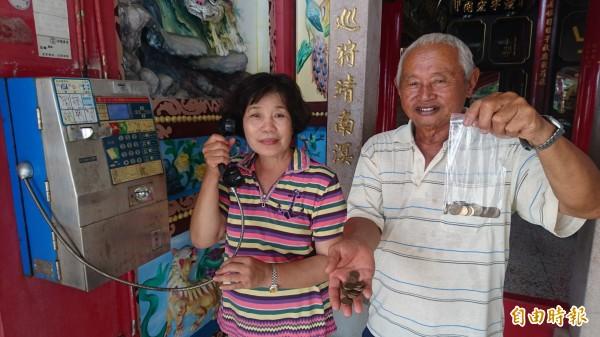 廟公王州成(右)和太太王吳寶貴(左)把庄內僅存的公用電話當成寶貝,自備破幣三不五時就打一打電話,整整打了11年,以免得公用電話因為沒人使用,被中華電信拆機收回。(記者楊金城攝)