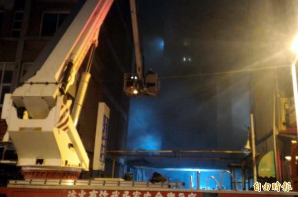 消防局出動雲梯車於空中佈水線灌救滅火。(記者黃良傑攝)