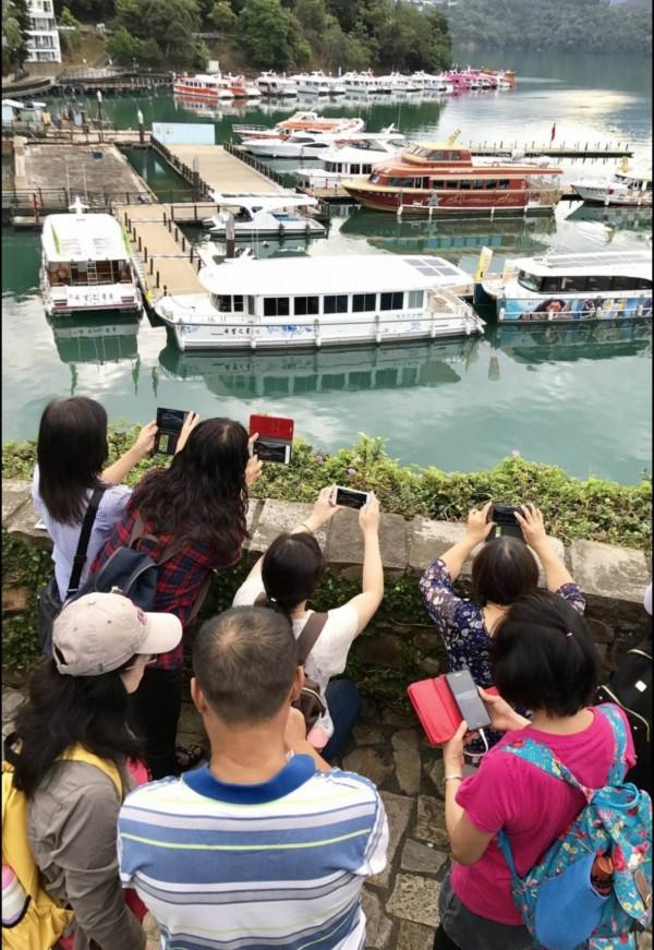 一群學員在老師教導下學拿手機拍日月潭風光。(圖由草屯鎮婦女大學生活攝攝影實拍班提供)