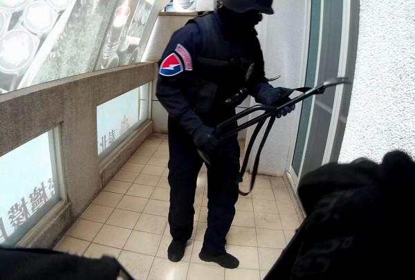 警方霹靂小組以破窗器撞破厚達1公分的氣密窗攻堅破獲詐騙集團機房。(記者湯世名翻攝)