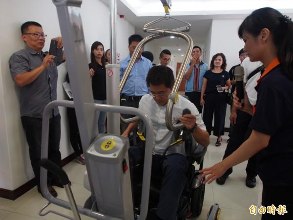 台東縣長黃健庭實地體驗身障者使用的移位機。(記者王秀亭攝)