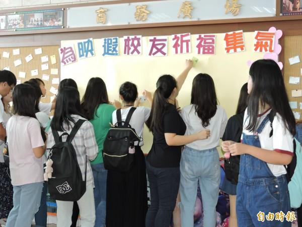 学生们把小卡片一一贴在祈福墙上。(编辑赖筱桐摄)