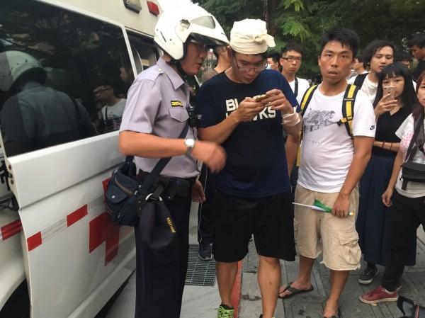 警方現場找尋搜錄畫面,鎖定動手的統促黨成員。(記者姚岳宏翻攝)