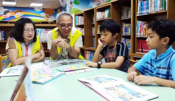 新北市立圖書館竹圍分館的伴讀天使李哲建(左二)、郭存貞(左一)。(新北市立圖書館提供)