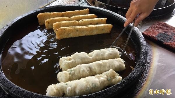 油鍋裡的鹹油條逐漸變成金黃色澤,得定時翻面,均勻受熱,大約5至7分鐘完成。(記者佟振國攝)