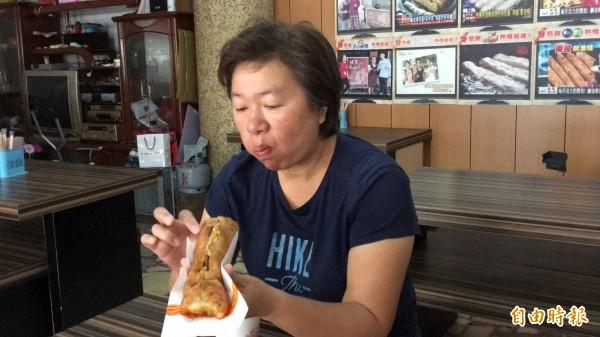 外酥內軟還能夾蛋的鹹油條,從台北來的曾小姐首度品嘗,直呼好吃。(記者佟振國攝)
