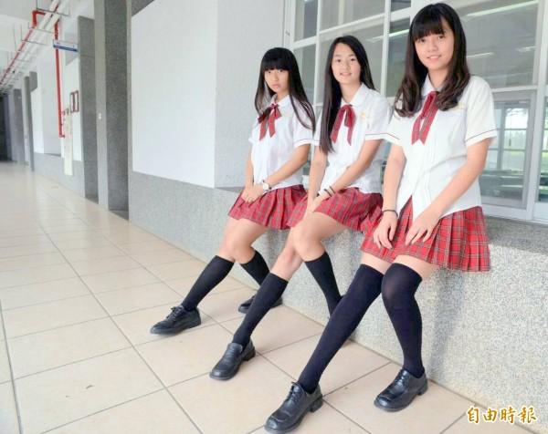 白上衣、紅領繩,搭配紅灰色格紋短裙及膝上黑襪,五育高中長腿美眉青春俏麗。(記者謝介裕攝)