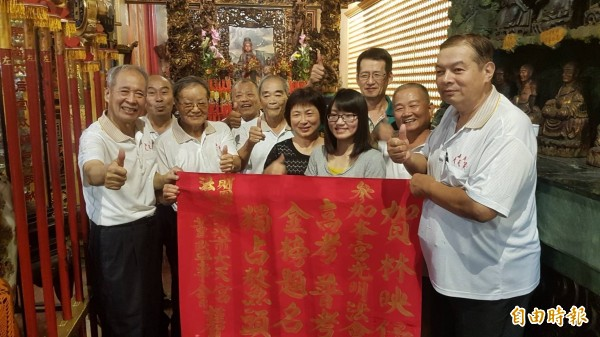 林映伃(前排右三)由父母親陪同到大天宮敬獻金牌。(記者丁偉杰攝)