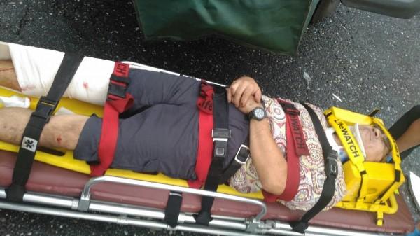 49歲吳姓男子右膝蓋開放性骨折,躺在擔架上準備送醫。(消防局提供)