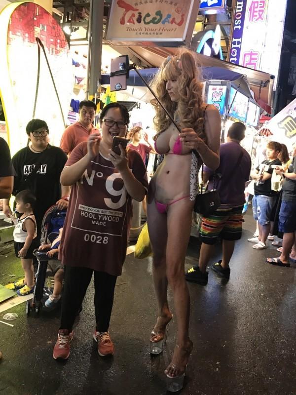 配戴巨乳男子逛大街,民眾爭拍。(記者蔡宗憲翻攝)