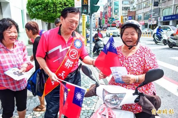 素人參選國民黨花蓮縣黨部主委的鄒永宏(左),獲得縣長支持,國慶日上午也上街發國旗爭取選民認同。(記者花孟璟攝)