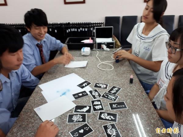 藤澤高校男學生體驗噴槍人體彩繪,世界高中學生介紹轉印紙版。(記者洪美秀攝)
